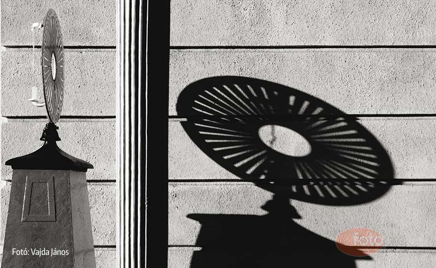 A függőleges építészeti díszítő elem szerencsésen osztja meg a képet. A bal oldalon jól érzékelhető, hogy mi veti az árnyékát a jobb oldalra, ugyanakkor az azon lévő fények és erőteljes árnyékok hiánya miatt szinte elveszne a majdnem ugyanolyan színű háttérben. Ez a fekete-fehér fénykép tónusainak különbségén is látható. Ezzel azonban a lényeg az ellenkező oldalon, erős kontrasztban megjelenő árnyképre helyeződik.